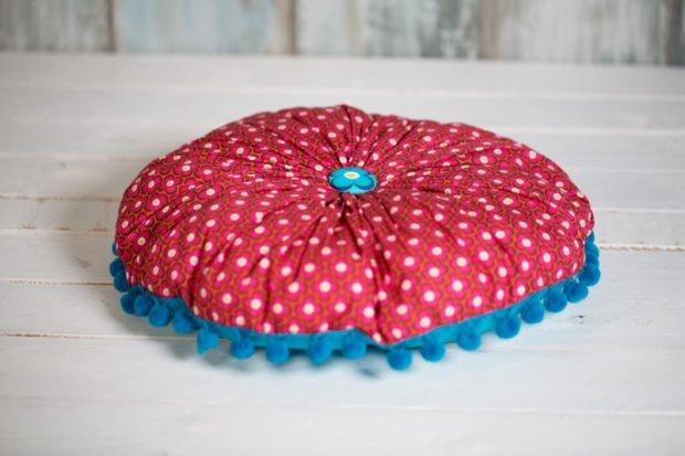 Nähanleitung für ein Blumenkissen von Pattydoo fertiggenäht mit rotem Stoff und blauen Bommeln.